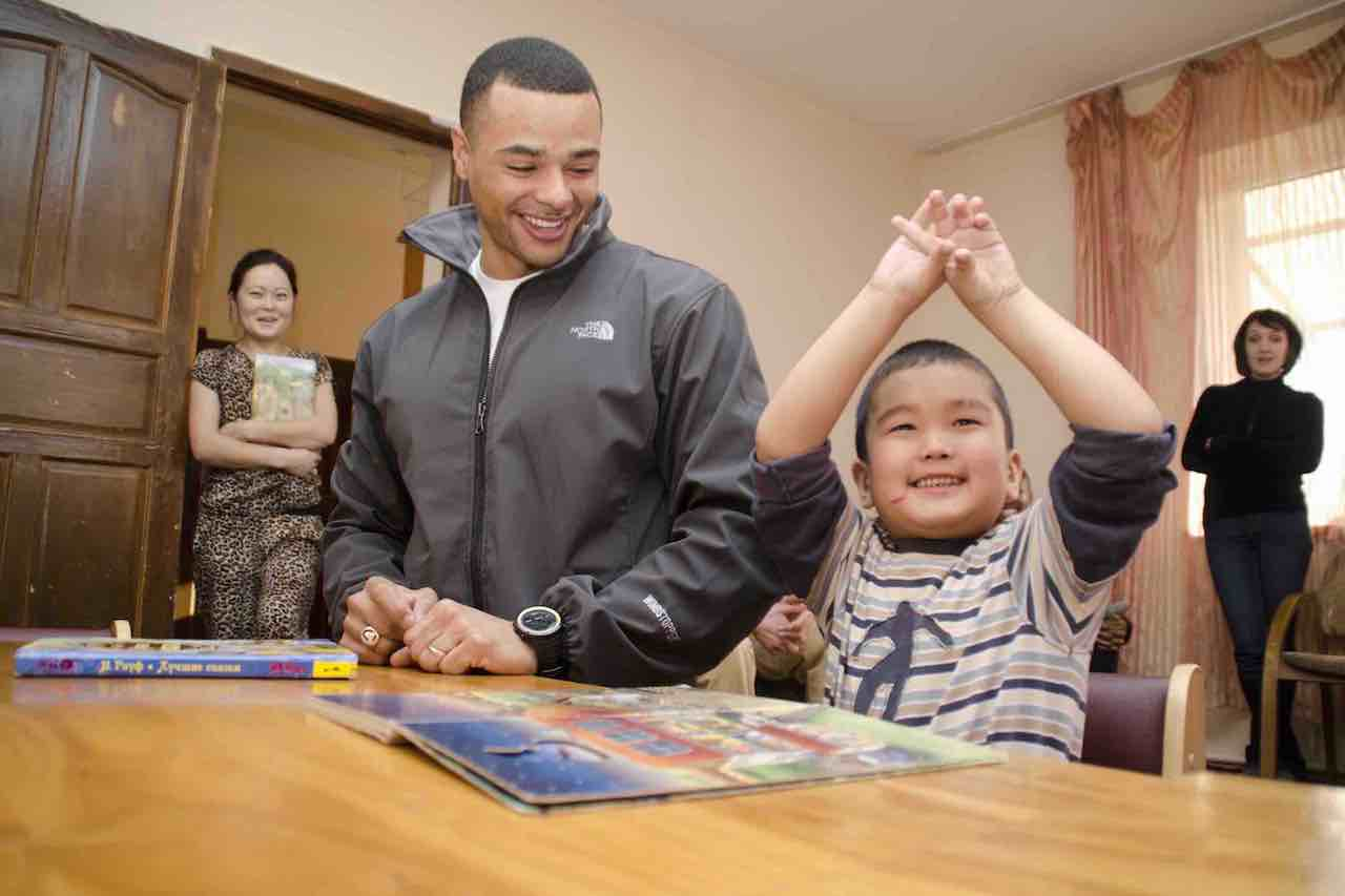 Army 1st Lt. Evan Howard, a deployed Ohio Army National Guardmember from Dayton, Ohio, reads a book with Daniar, a student at the Nadjeschda Children's Rehabilitation Center in Bishkek, Kyrgyzstan, Dec. 8, 2013. Howard and other Transit Center at Manas service members spent time with children from the school after delivering boxes of donated clothes and toys as part of the Rotary Club of Akron, Ohio's Operation Deployed for Good. (U.S. Air Force photo/Senior Airman Ross Whitley)