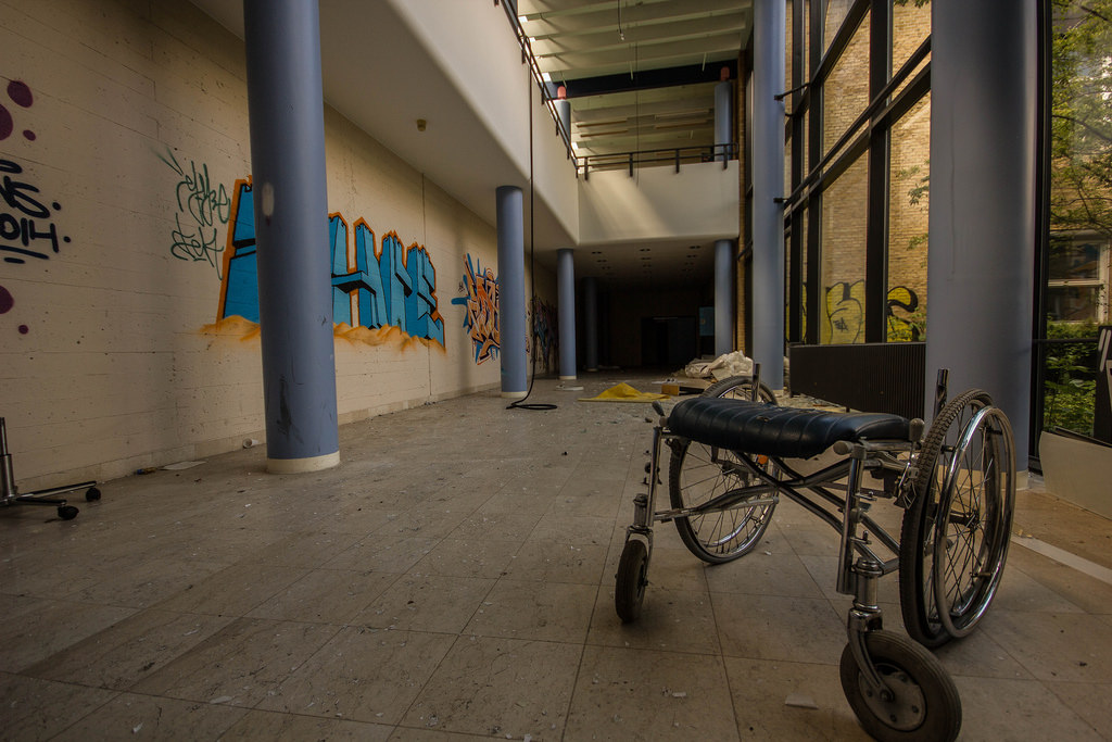 Discarded broken wheelchair in abandoned building.